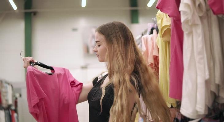 Девушка покупает футболку в магазине